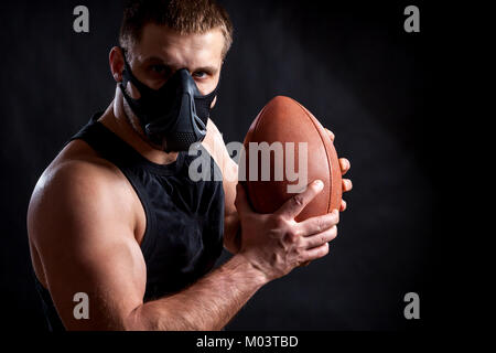 A dark-haired male athlete in a black training mask, a sports shirt holding a rugby ball on a black isolated background - Stock Photo