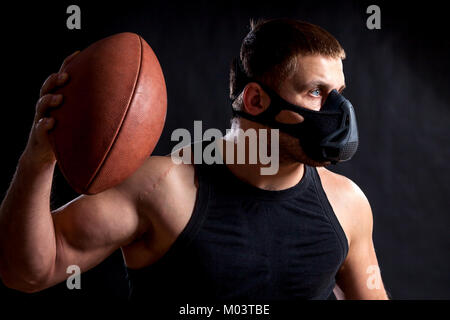 A dark-haired male athlete in a black training mask, a sports shirt holding a rugby ball and waving it on a black - Stock Photo