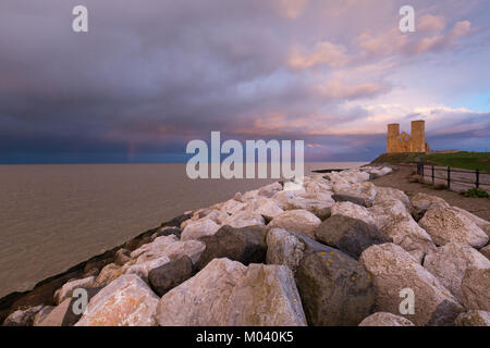 Bright light and dramatic pink and blue clouds over the twin towers of the Medieval church at Reculver, Kent, UK. - Stock Photo