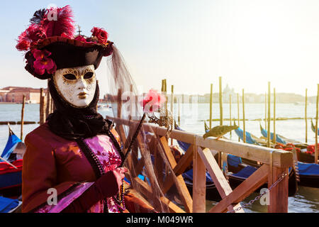 VENICE, ITALY - MARCH 04, 2011: Unidentified participant wears costume and mask in front of Grand canal during famous - Stock Photo
