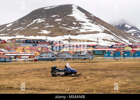 Colourful residential houses with snowmobile scooter parked on grass in old mining town of Longyearbyen, Spitsbergen - Stock Photo