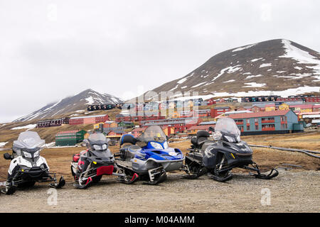 Motorised snowmobile scooters parked on roadside in summer in old mining town of Longyearbyen, Spitsbergen Island, - Stock Photo