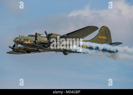 Boeing B-17 Flying Fortress 'Sally B' trailing smoke as part of it's display at Dunsfold Wings and Wheels, UK on - Stock Photo