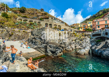 Tourists swim in the ligurian sea on the rocky coast of Manarola Italy, part of the Cinque Terre on the Italian - Stock Photo