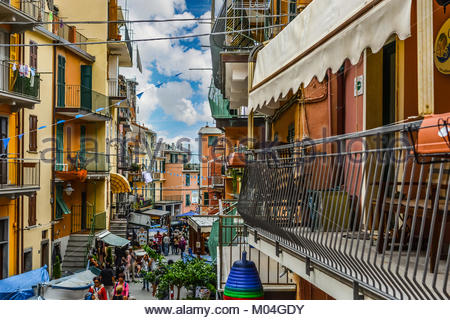 Balconies overlook the main street of Manarola Italy, part of the Cinque Terre, as tourists and locals enjoy an - Stock Photo