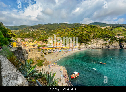 The sandy beach Spiaggia di Fegina, the railway with trains running, the mountains, sea and colorful village of - Stock Photo