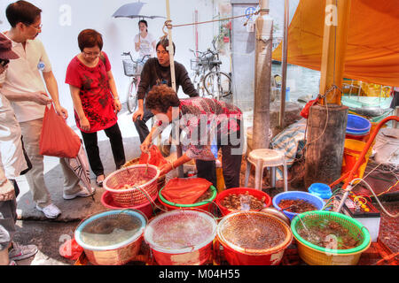 HONG KONG - APR 10, 2011: A street vendor in Tai O selling live seafood harvested from this seaside fishing village - Stock Photo