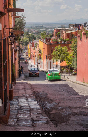Looking down a hilly cobblestone street, with old colorful buildings, a green taxi, people, cloudy sky and the valley - Stock Photo
