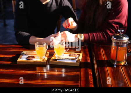 Couple sitting near table with sea-buckthorn broth in cafe discu - Stock Photo