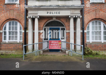 Closed down Police station with road ahead closed sign in entrance UK - Stock Photo