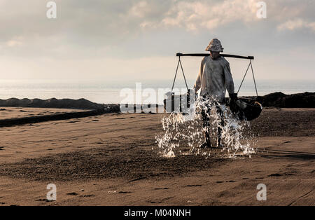 Indonesian salt farmer of Kusamba salt mining village in Bali collecting sea water in the morning for producing - Stock Photo