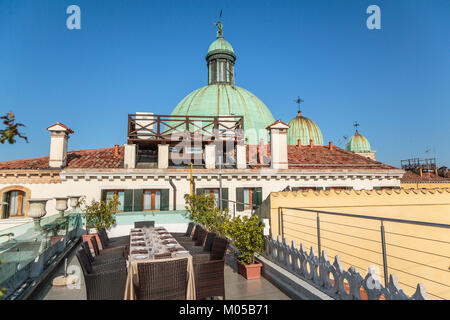 Church domes of the Church of San Simeone Piccolo and rooftop tables at the Hotel Carlton along the Grand Canal - Stock Photo