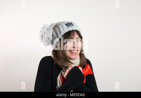 Interior front view happy caucasian female in 30s, in woolly hat, hugging hot water bottle close to chest. Nice - Stock Photo
