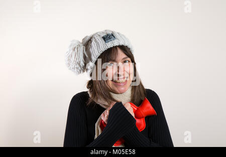 Interior front view of happy caucasian female in 30s, in woolly knitted bobble hat, hugging red hot water bottle - Stock Photo
