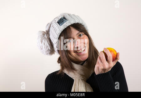 Indoor portrait of happy, healthy long-haired female, in woolly bobble hat & scarf, holding fresh apple in hand - Stock Photo