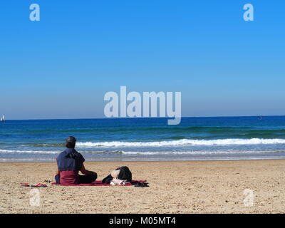 recreation on vacation - couple is lying and sitting together in the sun on a sandy beach - Stock Photo