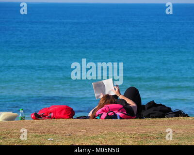 girl lying in the sun at the promenade near the beach in front of the sea on a perfect day with clear blue sky