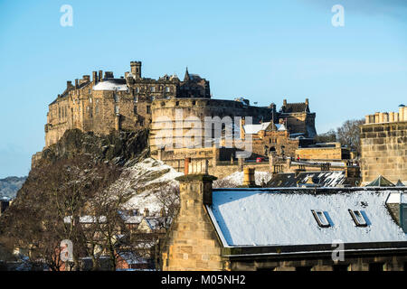 View of Edinburgh Castle across snow covered roofs of houses , Scotland, United Kingdom - Stock Photo