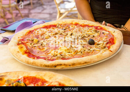 Pizza with mushrooms and ham on a plate in a restaurant - Stock Photo
