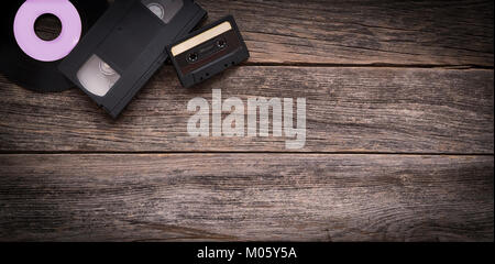 Vinyl record, video cassette and audio tape on a wooden background - Stock Photo