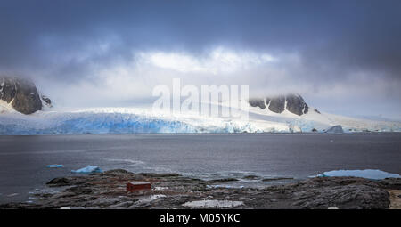 Rocky coastline panorama with mountains and glaciers hidden in clouds, Peterman island, Antarctic peninsula - Stock Photo