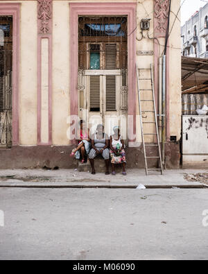Three Afro Caribbean females relax on a stone step outside a doorway to a property in Havana, Cuba - Stock Photo