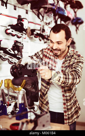 Young satisfied pleasant smiling male repairer fixing roller-skates in sports store - Stock Photo