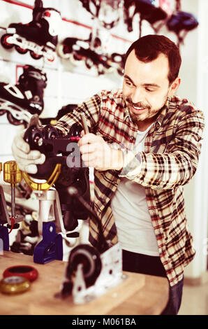 Young pleasant smiling male repairer fixing roller-skates in sports store - Stock Photo