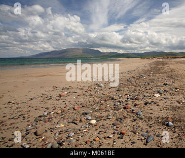 Deserted pebble beach on a sunny day with clouds on the Dingle Peninsula on the west coast of Ireland - Stock Photo