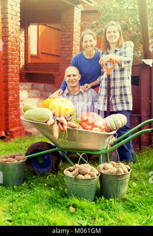 Man and two women with  harvested vegetables in garden - Stock Photo