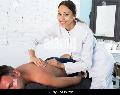Professional masseuse performing back massage to male client in spa center - Stock Photo