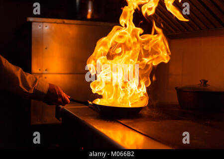 Flambe lamb rib roast. Cooking with fire in frying pan. Professional chef in a commercial kitchen cooking. Man frying - Stock Photo