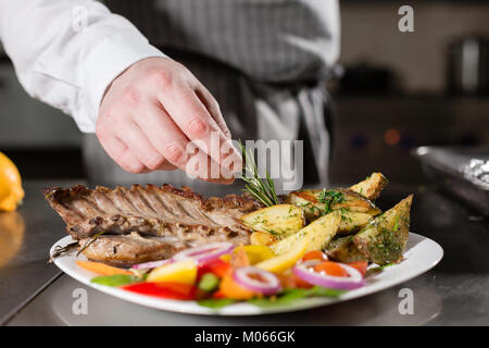 the chef prepares in the restaurant. Grilled rack of lamb with fried potatoes and fresh vegetables. closeup - Stock Photo