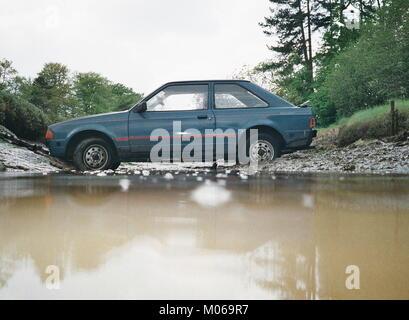 AJAXNETPHOTO. 1991.HAMBLE, ENGLAND. - CAR IN CREEK. - A FORD ESCORT LIES IN A TIDAL RIVER CREEK AFTER COMING OFF - Stock Photo