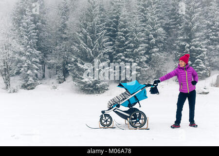 Mother with baby stroller enjoying motherhood in winter forest, mountains landscape. Jogging or power walking woman - Stock Photo