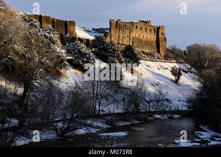 Richmond Castle, in the snow, overlooking the river Swale - Stock Photo