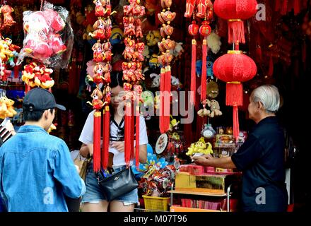 Young Chinese couple buying lunar new year decorations at a store in Chinatown, Singapore - Stock Photo