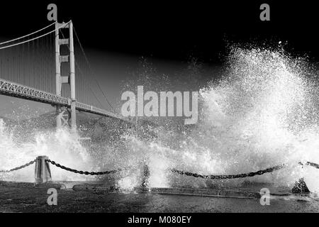 Golden Gate Bridge. Huge waves crash over the sea wall below the bridge in the foreground . Black and white monochrome - Stock Photo