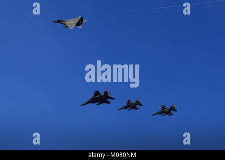 U.S. F-15C Eagles from the 493rd Expeditionary Fighter Squadron peel away from a formation with Royal Danish F-16's - Stock Photo