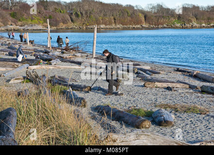 Man with metal detector at one of the beaches in Greater Victoria, BC, Canada. - Stock Photo