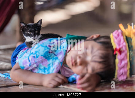 Portrait of long neck tribal girl sleeping in her village, Thailand - Stock Photo