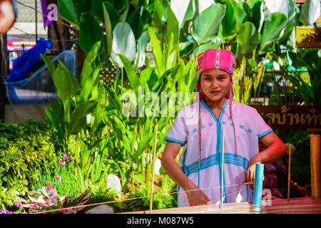 CHIANGMAI, THAILAND - JANUARY 24, 2015: Hill tribe girl is demonstrating weaving  faric in traiditional style in - Stock Photo