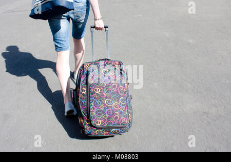 Belgrade, Serbia - September 17, 2017 : Young woman in bermuda jeans shorts with rolling luggage wheeled suitcase - Stock Photo