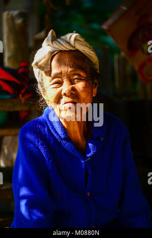 CHIANGMAI, THAILAND - JANUARY 24, 2015: Indigenous senior woman in light and shadow looking to visitors in Mae Chaem - Stock Photo