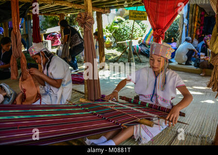 CHIANGMAI, THAILAND - JANUARY 24, 2015: Hill tribe girl is demonstrating weaving in 22nd Traditional Skirt Fabric - Stock Photo