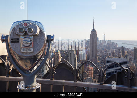 NEW YORK - SEPTEMBER 12: Binoculars on Rockefeller Center with Empire State Building and city view in the late afternoon - Stock Photo