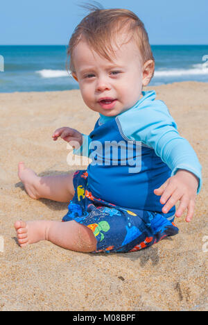 Baby Boy Wearing Blue Shirt Playing in the Sand at the Beach - Stock Photo