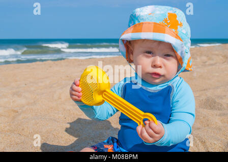 Baby Boy Wearing Blue Shirt Playing with Toys in the Sand at the Beach - Stock Photo