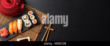Set of sushi with wasabi, soy sauce and teapot on black stone background - Stock Photo