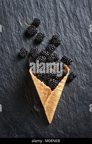 Blackberry explosion. Photo of blackberry in waffle cone on black slate. Top view. High resolution product. - Stock Photo